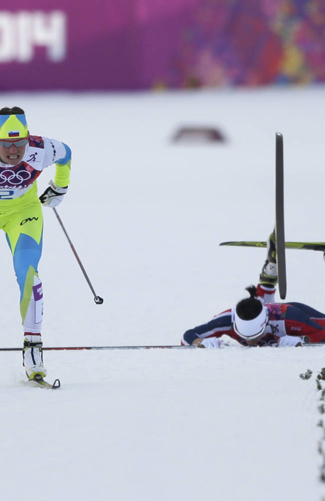 Norway's Marit Bjoergen, right, falls as Slovenia's Katja Visnar passes by during their women's semifinal heat of the cross-country sprint at the 2014 Winter Olympics, Tuesday, Feb. 11, 2014, in Krasnaya Polyana, Russia