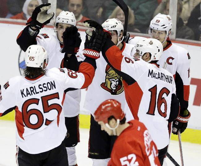 Clockwise from left, Ottawa Senators defenseman Erik Karlsson (65), of Sweden, center Kyle Turris, right wing Bobby Ryan, center Jason Spezza, and left wing Clarke MacArthur (16) celebrate Ryan's goal during the third period of an NHL hockey game in Detroit, Saturday, Nov. 23, 2013. In the foreground is Detroit Red Wings defenseman Jonathan Ericsson, of Sweden