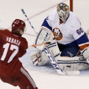 New York Islanders' Kevin Poulin (60) makes a save on a shot by Phoenix Coyotes' Radim Vrbata (17), of the Czech Republic, during the third period of an NHL hockey game Thursday, Dec. 12, 2013, in Glendale, Ariz. The Coyotes defeated the Islanders 6-3 Th