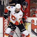 Calgary Flames left wing Brandon Bollig (25) controls the puck against Chicago Blackhawks left wing Daniel Carcillo during the first period of an NHL hockey game in Chicago, Wednesday, Oct. 15, 2014 The Associated Press