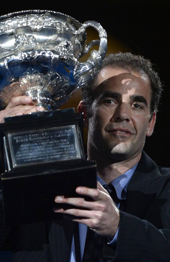Former world No.1 Pete Sampras carries the championship trophy onto the Rod Laver Arena prior to the the men's singles final between Rafael Nadal of Spain and Stanislas Wawrinka of Switzerland at the Australian Open tennis championship in Melbourne, Australia, Sunday, Jan. 26, 2014