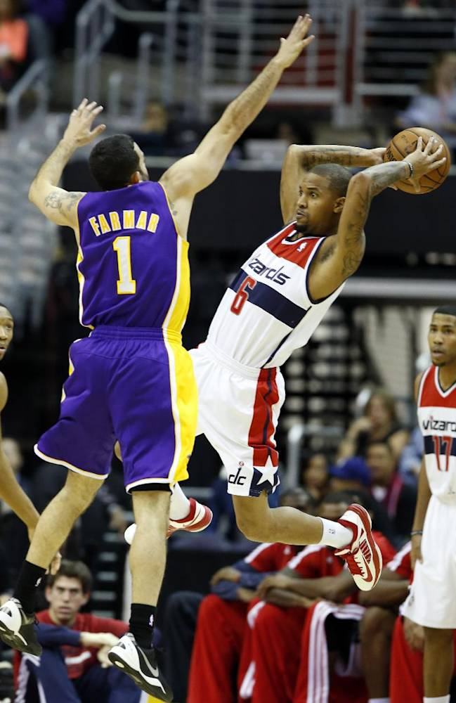 Washington Wizards guard Eric Maynor (6) passes the ball in front of Los Angeles Lakers guard Jordan Farmar (1) in the first half of an NBA basketball game Tuesday, Nov. 26, 2013, in Washington