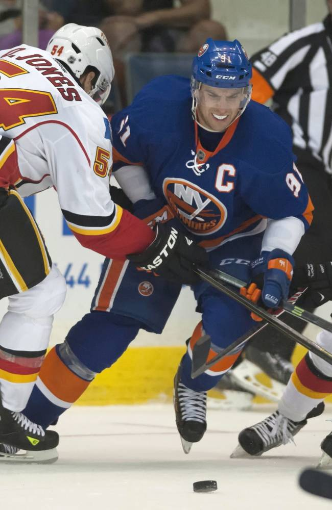 Calgary Flames forwards David Jones, left, and Max Reinhart, right, attempt to slow down New York Islanders forward John Tavares during the third period of an NHL hockey game Tuesday, Sept. 17, 2013, in Regina, Saskatchewan. The Flames won 4-2