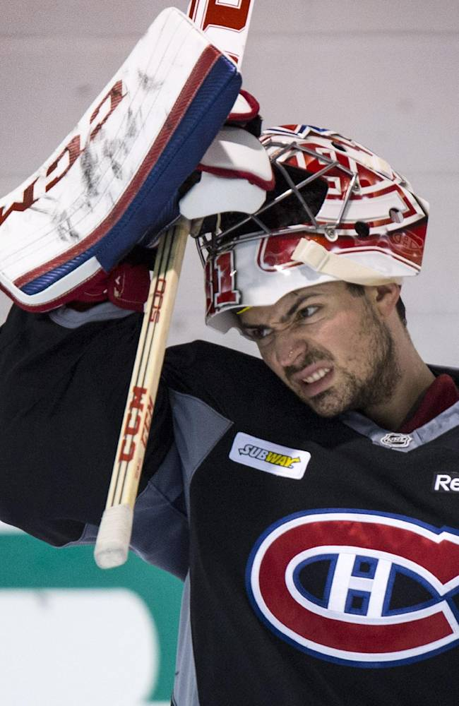 Montreal Canadiens goalie Carey Price slips on his face mask during NHL hockey practice Wednesday, April 30, 2014, in Brossard, Quebec The Canadiens face the Boston Bruins in Game 1 in the second round of the Stanley Cup playoffs Thursday in Boston