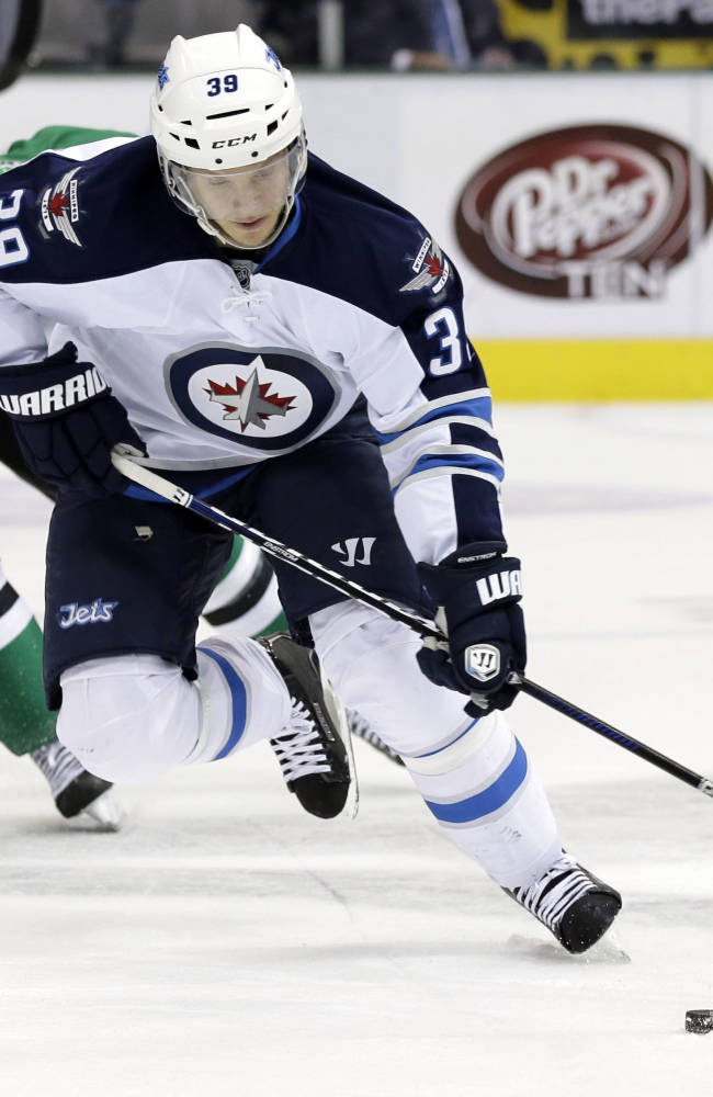 Winnipeg Jets' Tobias Enstrom (39), of Sweden, controls the puck as Dallas Stars center Vernon Fiddler (38) gives chase in the first period of an NHL hockey game, Saturday, Oct. 26, 2013, in Dallas