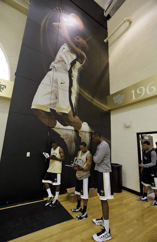 Wake Forest players, from right, Daniel Green, Coron Williams, and Codi Miller-McIntyre, look over media guides as they stand under a photo of former team star Chris Paul during the NCAA college basketball media day in Winston-Salem, N.C., Tuesday, Oct. 8, 2013