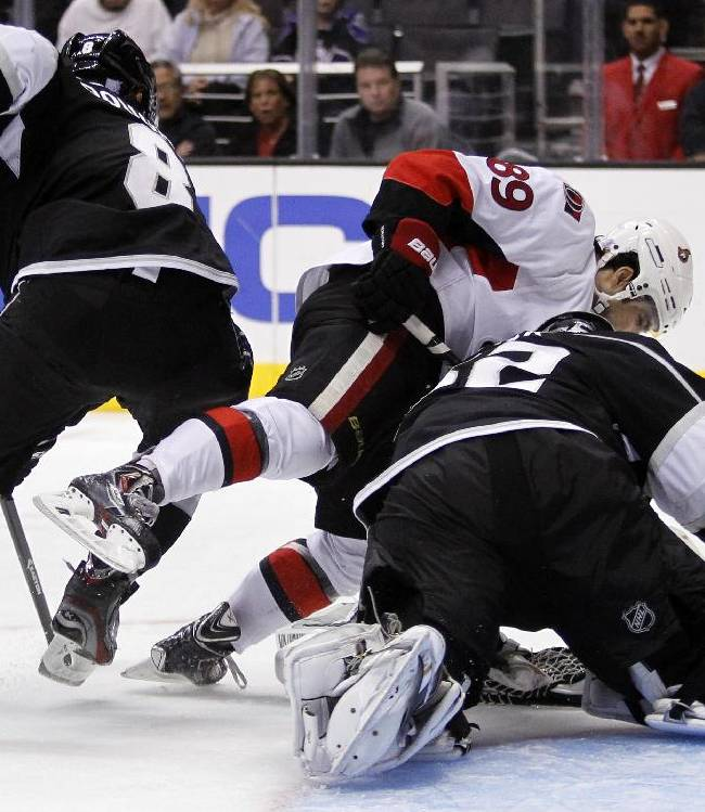 Ottawa Senators left wing Cory Conacher, center, attempts to steal the puck from Los Angeles Kings goalie Jonathan Quick, right, with Kings defenseman Drew Doughty, left, defending during the third period of their NHL hockey game, Wednesday, Oct. 9, 2013, in Los Angeles. Kings won the game 4-3 in overtime