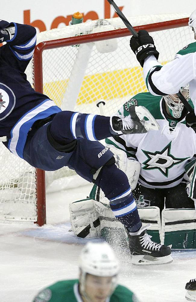 Dallas Stars' Aaron Rome (27) clears Winnipeg Jets' Devin Setoguchi (40) from in front of Stars' goaltender Kari Lehtonen (32) during first period of an NHL hockey game in Winnipeg, Manitoba, on Saturday, Dec. 14, 2013