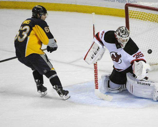 Buffalo Sabres center Tyler Ennis (63) scores on New Jersey Devils goaltender Cory Schneider (35) during the team shootout of an NHL hockey game in Buffalo, N.Y., Tuesday, April 1, 2014.  Buffalo won 3-2
