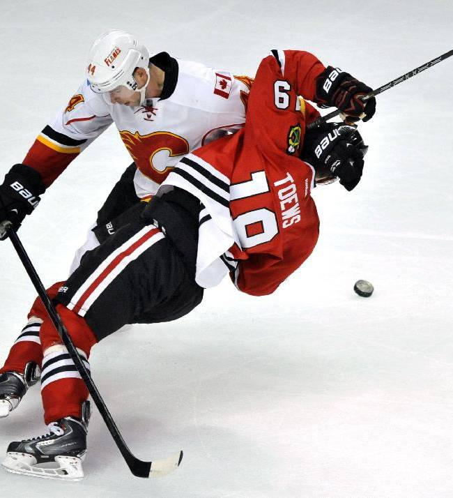Chicago Blackhawks' Jonathan Toews, right, battles Calgary Flames' Chris Butler for the puck during the third period of an NHL hockey game in Chicago, Sunday, Nov. 3, 2013. Calgary won 3-2 in overtime