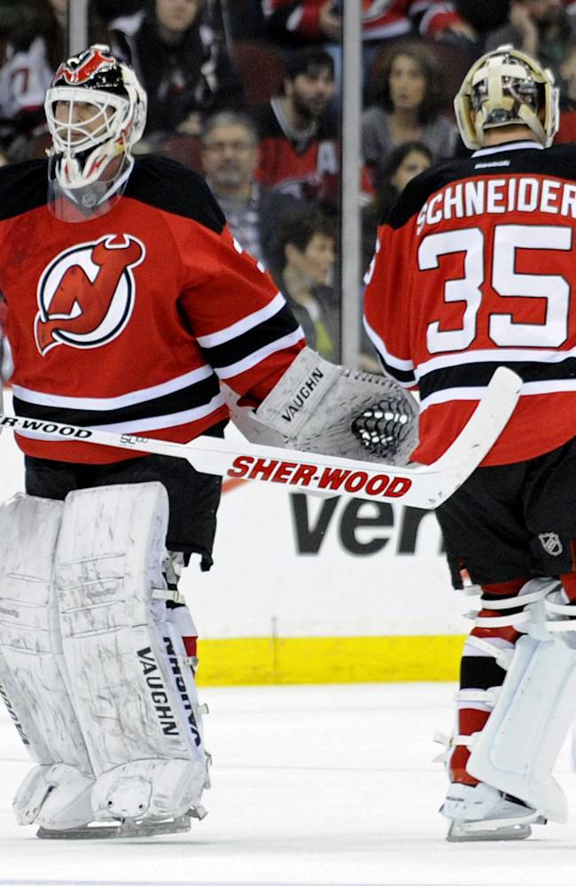 New Jersey Devils goaltender Martin Brodeur, left, leaves the game as he is replaced by Cory Schneider during the second period of an NHL hockey game against the Florida Panthers Monday, March 31, 2014, in Newark, N.J