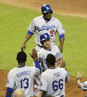 Los Angeles Dodgers' Juan Uribe (5) and Skip Schumaker (55) are met by Hanley Ramirez (13) and Yasiel Puig (66) after scoring on a double by Carl Crawford in the fourth inning during a baseball game against the Miami Marlins, Thursday, Aug. 22, 2013 in Miami. (AP Photo/Lynne Sladky)