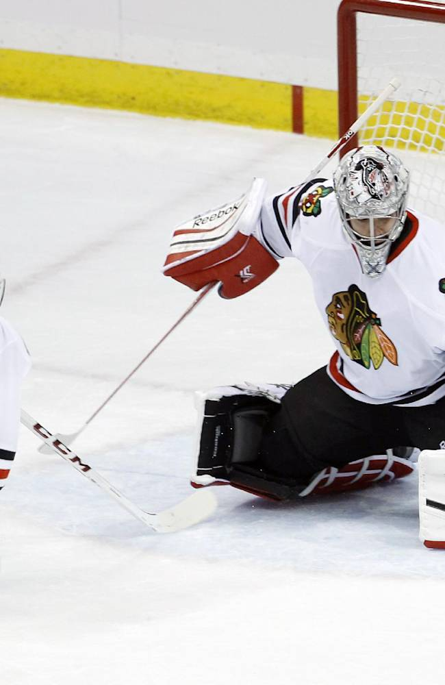 Chicago Blackhawks goalie Corey Crawford (50) deflects a shot by Minnesota Wild left wing Erik Haula (56), of Finland, in front of Blackhawks defenseman Duncan Keith (2) during the first period of Game 3 of an NHL hockey second-round playoff series in St. Paul, Minn., Tuesday, May 6, 2014