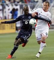 Sporting KC's Ike Opara (3) and New England Revolution's Chad Barrett (9) battle for the ball in the first half of an MLS soccer match in Foxborough, Mass., Saturday, March 23, 2013. (AP Photo/Michael Dwyer)