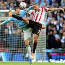 Sunderland's Wes Brown, right, vies for the ball with Manchester City's Edin Dzeko, left, during their English League Cup final soccer match at Wembley Stadium, London, England, Sunday, March 2, 2014