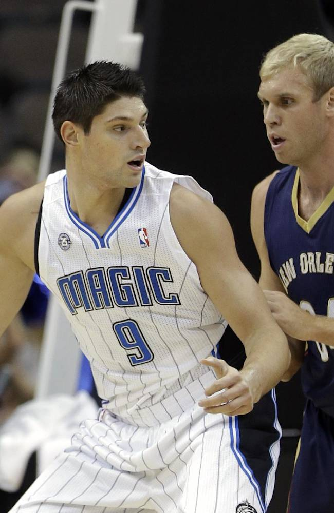 Orlando Magic's Nikola Vucevic (9) looks for a way around New Orleans Pelicans' Greg Stiemsma during the first half of an NBA preseason basketball game in Jacksonville, Fla., Wednesday, Oct. 9, 2013
