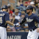 San Diego Padres' Yonder Alonso is congratulated by Nick Hundley after scoring during the first inning of a spring exhibition baseball game against the Kansas City Royals Wednesday, March 26, 2014, in Peoria, Ariz The Associated Press