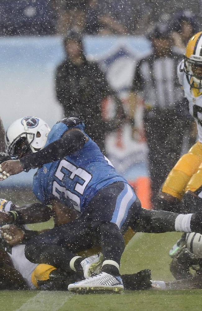 In the rain, Green Bay Packers running back James Starks, lower left, scores a touchdown on a 20-yard run against the Tennessee Titans in the first quarter of a preseason NFL football game Saturday, Aug. 9, 2014, in Nashville, Tenn. Titans cornerback Jason McCourty (30) and safety Michael Griffin (33) defend on the play