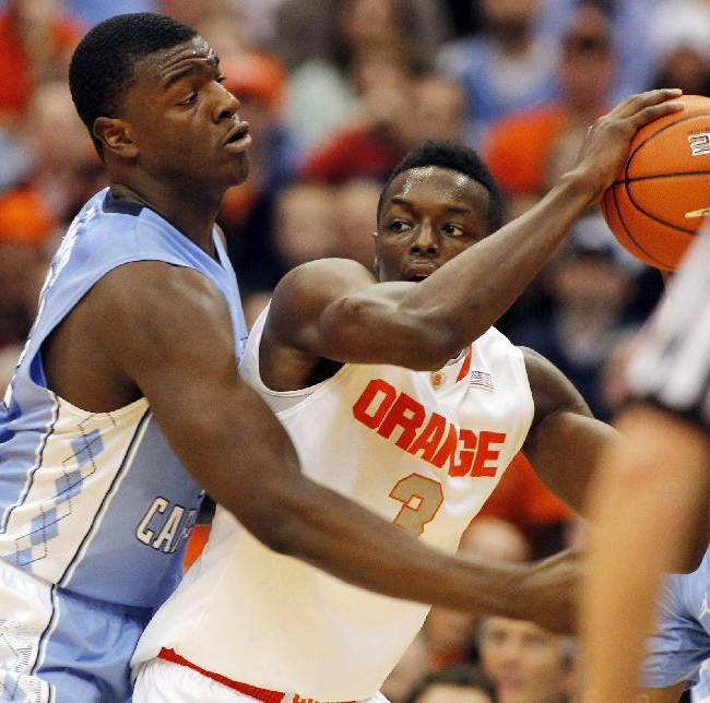 Syracuse's Jerami Grant, right, looks to pass the ball under pressure from North Carolina's Joel James, left, in the first half of an NCAA college basketball game in Syracuse, N.Y., Saturday, Jan. 11, 2014