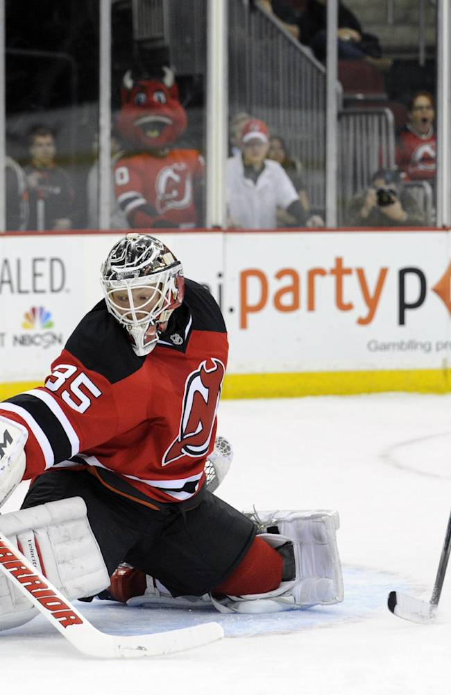 New Jersey Devils goaltender Cory Schneider, left, makes a save as Columbus Blue Jackets' R.J. Umberger looks for a rebound during the first period of an NHL hockey game on Thursday, Feb. 27, 2014, in Newark, N.J