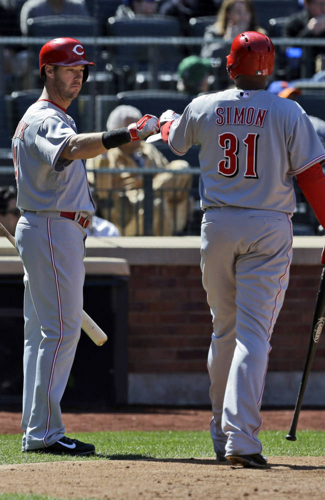 Cincinnati Reds' Alfredo Simon, right, celebrates with teammate Ryan Ludwick after scoring on a sacrifice fly hit by Joey Votto during the sixth inning of the baseball game against the New York Mets at Citi Field, Sunday, April 6, 2014, in New York