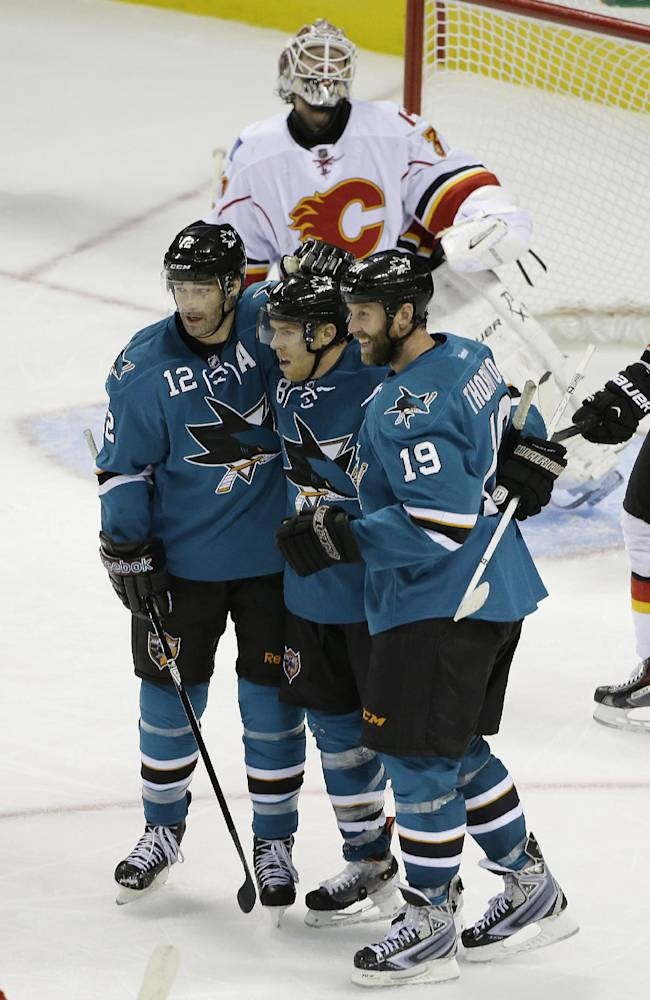 San Jose Sharks center Joe Pavelski is greeted by teammates Patrick Marleau (12) and Joe Thornton (19) after scoring the Sharks' fifth goal during the third period of an NHL hockey game Saturday, Oct. 19, 2013, in San Jose, Calif. Looking on in the background is Calgary Flames goalie Karri Ramo. San Jose won the game 6-3