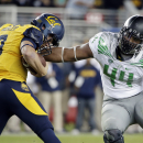 California quarterback Luke Rubenzer, left, tries to evade the tackle of Oregon defensive lineman DeForest Buckner (44) during the first half of an NCAA college football game Friday, Oct. 24, 2014, in Santa Clara, Calif The Associated Press
