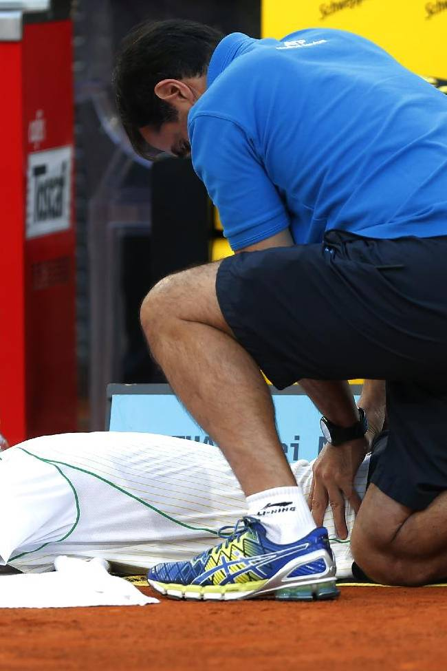 Kei Nishikori from Japan gets help from a physiotherapist during his Madrid Open tennis tournament final match against Rafael Nadal from Spain in Madrid, Spain, Sunday, May 11, 2014