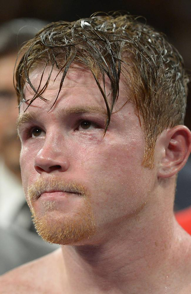 Canelo Alvarez listens as Floyd Mayweather Jr. is announced as the winner of their 152-pound title fight, Saturday, Sept. 14, 2013, in Las Vegas