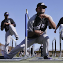 Colorado Rockies pitcher Manuel Corpas, center, ducks under a hurdle in front of teammates LaTroy Hawkins, left, and Greg Burke, right, during spring training baseball practice, Monday, Feb. 17, 2014, in Scottsdale, Ariz The Associated Press