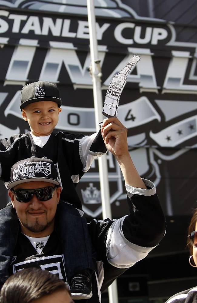 Los Angeles Kings NHL hockey fans cheer as the team make their way during a parades with the Stanley Cup trophy downtown Los Angeles, Monday, June 16, 2014. The parade and rally were held to celebrate the Kings' second Stanley Cup championship in three seasons. The Kings defeated the New York Rangers for the title