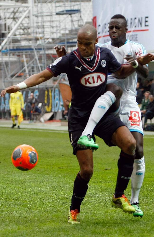 Marseille's French defender Benjamin Mendy, right, challenges for the ball with Bordeaux's Brazilian defender Carlos Henrique dos Santos Souza, during their League One soccer match, at the Velodrome Stadium, in Marseille, southern France, Sunday, Dec. 22, 2013