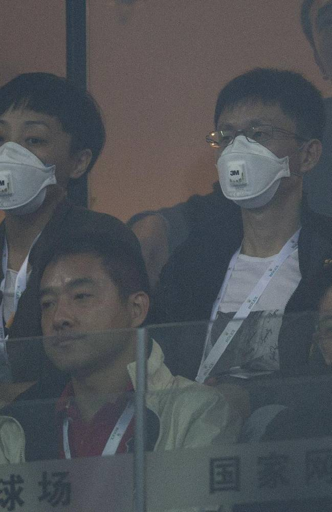 Spectators wear mask watching a semifinal match between Novak Djokovic of Serbia and Richard Gasquet of France in the China Open tennis tournament at the National Tennis Stadium, shrouded by haze in Beijing, China Saturday, Oct. 5, 2013