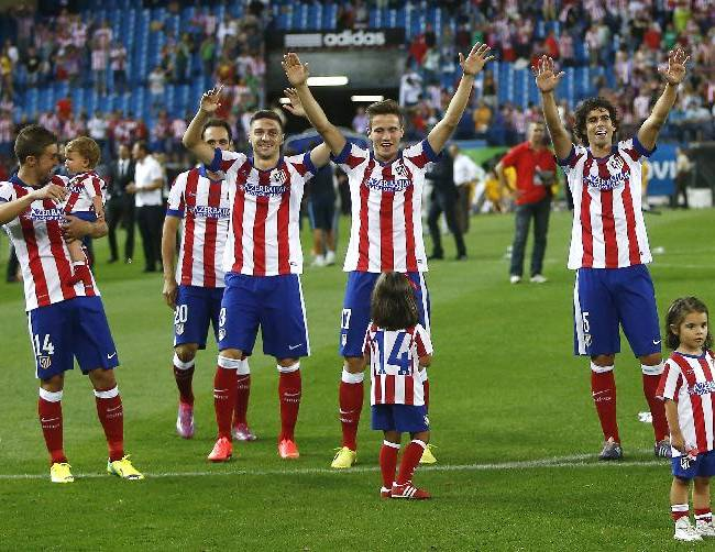 Atletico' players celebrates their victory during a Spanish Supercup second leg soccer match between Real Madrid and Atletico Madrid at Vicente Calderon stadium in Madrid, Spain, early Saturday, Aug. 23, 2014