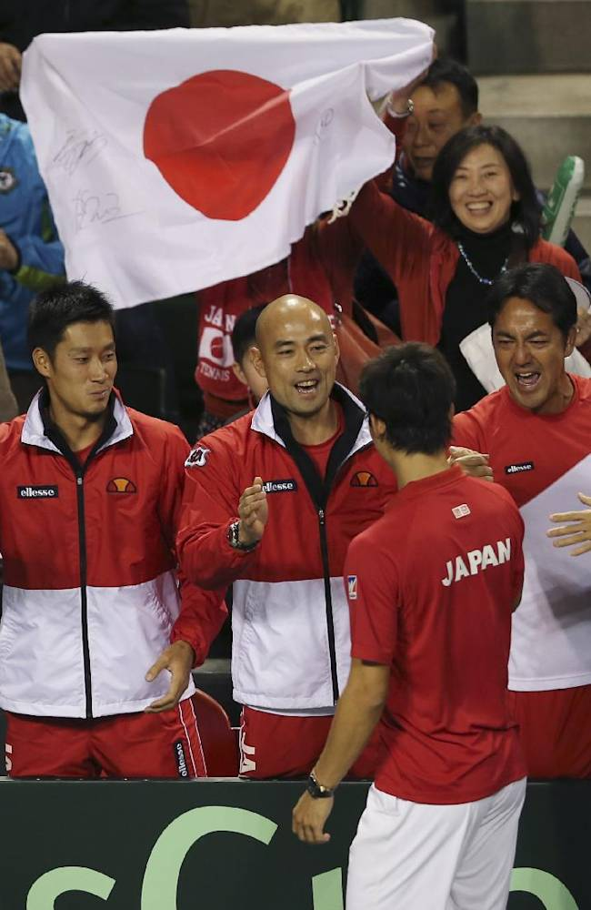 Japan's Kei Nishikori, facing back, is greeted by his team members after their win over Canada during their 1st round of Davis Cup World Group doubles tennis match in Tokyo, Saturday, Feb. 1, 2014