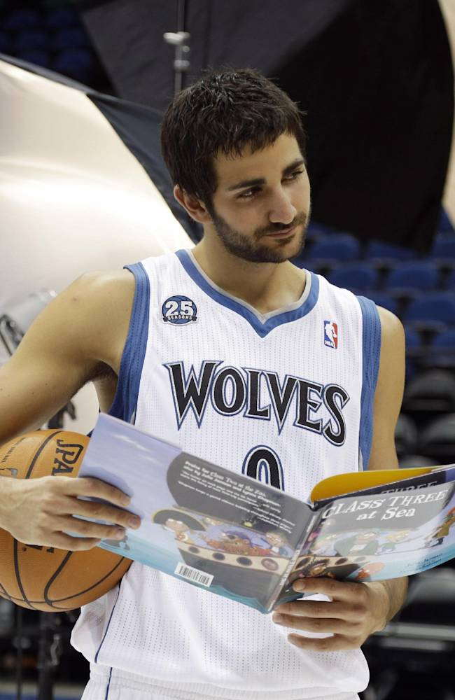 Minnesota Timberwolves' Ricky Rubio of Spain poses for the team photographer with a basketball and childrens' book during the NBA basketball team's media day, Monday, Sept. 30, 2013, in Minneapolis