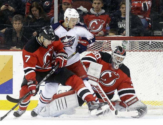 Columbus Blue Jackets right wing Corey Tropp, center, is defended by New Jersey Devils defenseman Mark Fayne, left, and goalie Martin Brodeur during the second period of an NHL hockey game, Friday, Dec. 27, 2013, in Newark, N.J