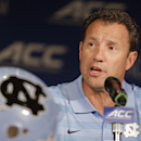 FILE - In this July 21, 2014, file photo, North Carolina coach Larry Fedora answers a question during a news conference at the Atlantic Coast Conference football kickoff in Greensboro, N.C. Fedora says the team has suspended four players for this weekend's season opener, a day after a report of an alleged hazing altercation left a walk-on receiver with a possible concussion. Fedora said Wednesday, Aug. 27, the four players were suspended for a