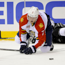 Florida Panthers defenseman Dmitry Kulikov (7), of Russia, attempts to control the puck after battling Los Angeles Kings right wing Dustin Brown, back, for it during the second period of an NHL hockey game on Saturday, March 22, 2014, in Los Angeles The