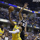 Indiana Pacers forward Paul George, left, is fouled from behind by San Antonio Spurs forward Tim Duncan in the first half of an NBA basketball game in Indianapolis, Monday, March 31, 2014 The Associated Press