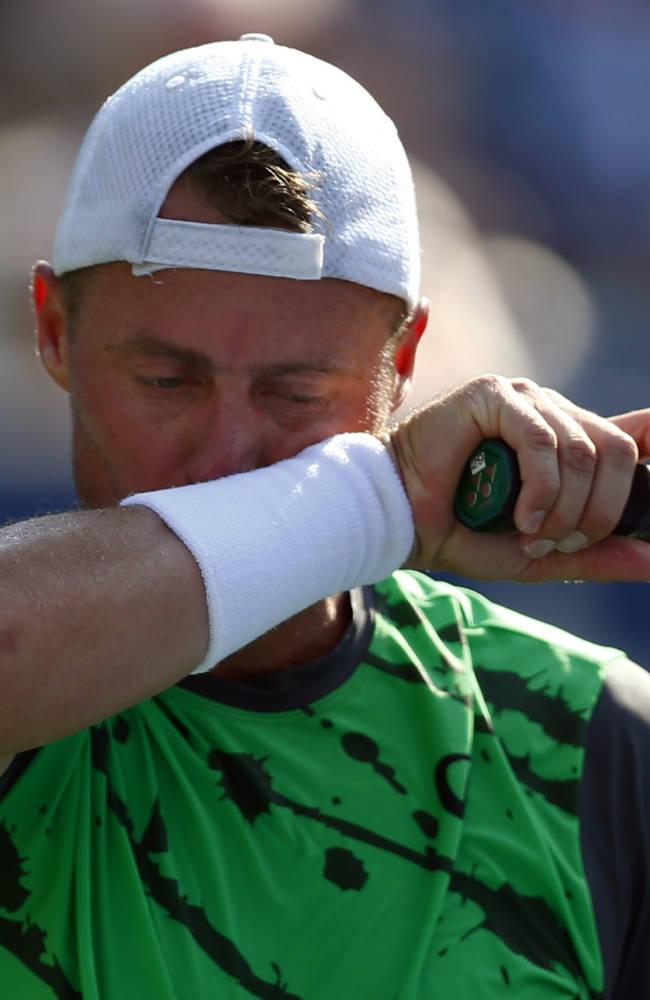 Lleyton Hewitt, of Australia, wipes sweat from his face between points against Tomas Berdych, of the Czech Republic, during the second round of the 2014 U.S. Open tennis tournament, Wednesday, Aug. 27, 2014, in New York