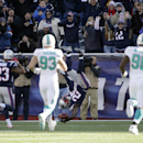 New England Patriots cornerback Kyle Arrington (25) dives into the end zone for a touchdown after returning a blocked field goal-attempt between Miami Dolphins middle linebacker Jason Trusnik (93) and defensive tackle Earl Mitchell (90) in the first half