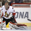 Ottawa Senators' Craig Anderson makes a save on a shot by the Arizona Coyotes as the puck bounces off his face mask during the first period of an NHL hockey game Saturday, Jan. 10, 2015, in Glendale, Ariz The Associated Press