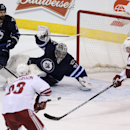 Winnipeg Jets' goaltender Ondrej Pavelec (31) sprawls across the net to try to stop Arizona Coyotes' Oliver Ekman-Larsson (23) and Shane Doan (19) with Jets' Jay Harrison (23) in front of the net during first-period NHL hockey game action in Winnipeg, Man