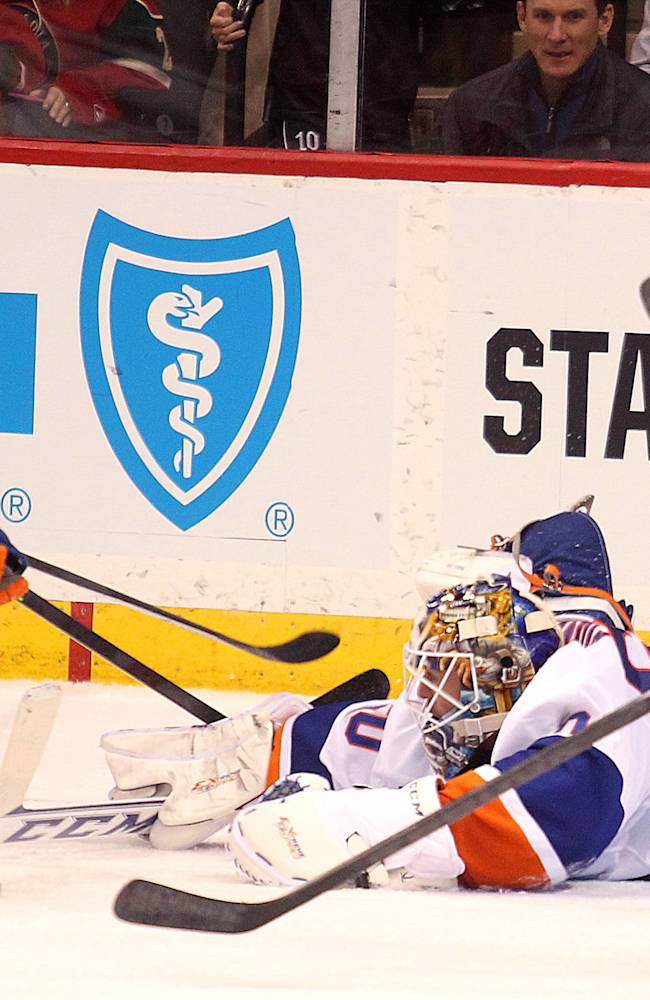 Minnesota Wild forward Justin Fontaine, left, scores a goal on a diving New York Islanders goalie Kevin Poulin during the third period of their NHL hockey game won by the Islanders 5-4, Sunday, Dec. 29, 2013, in St. Paul, Minn