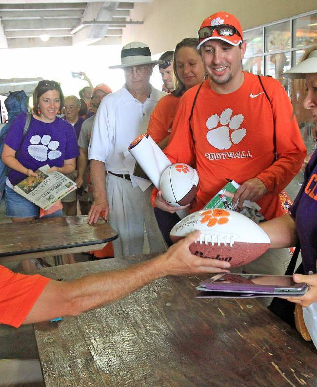 Clemson NCAA college football head coach Dabo Swinney, left, laughs as he hands an autographed football to a fan at the Tigers' Fan Appreciation Day at Memorial Stadium in Clemson, S.C. on Sunday, Aug, 17, 2014
