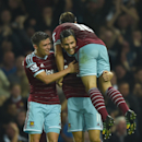 West Ham United's Stewart Downing, centre, celebrates setting up his team's third goal, with West Ham United's Aaron Cresswell, left, and West Ham United's Mark Noble, right, during their English Premier League soccer match against Liverpool at Upton Park