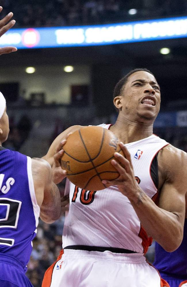 Toronto Raptors' DeMar DeRozan, center, drives to the net past Sacramento Kings' Isaiah Thomas, left, as Kings' Rudy Gay and Raptors Kyle Lowry, right, look on during first half NBA basketball action in Toronto on Friday, March 7, 2014