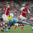 Arsenal's Mathieu Debuchy, left, and Alexis Sanchez, right, in action with Crystal Palace's Yannick Bolasie, during their English Premier League soccer match, at Emirates Stadium, in London, Saturday, Aug. 16, 2014