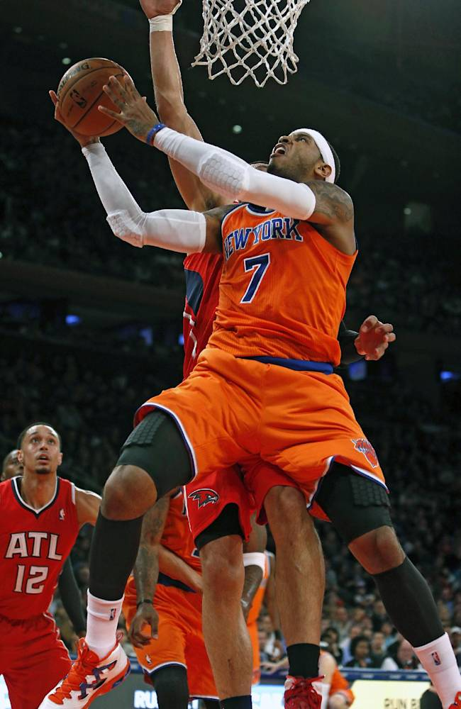 New York Knicks' Carmelo Anthony (7) shoots against Atlanta Hawks' Gustavo Ayon, behind, during the first half of an NBA basketball game Saturday, Nov. 16, 2013, in New York